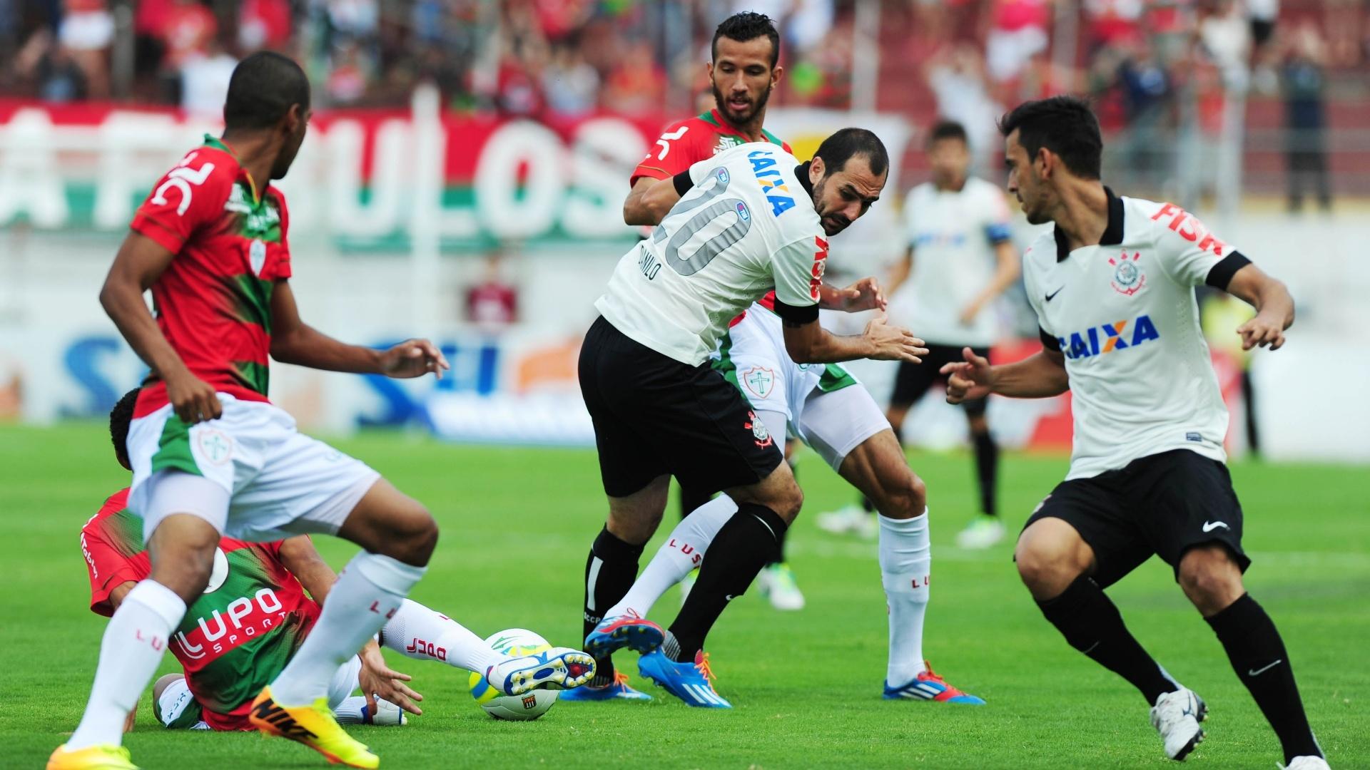 19.jan.2014 - Jogadores de Corinthians e Portuguesa disputam bola no meio de campo durante partida pelo Campeonato Paulista