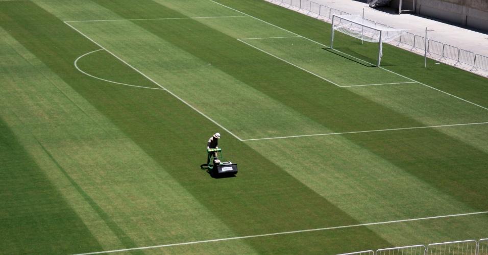 22.jan.2014 - Antes da inauguração, trabalhadores fazem reparos no gramado