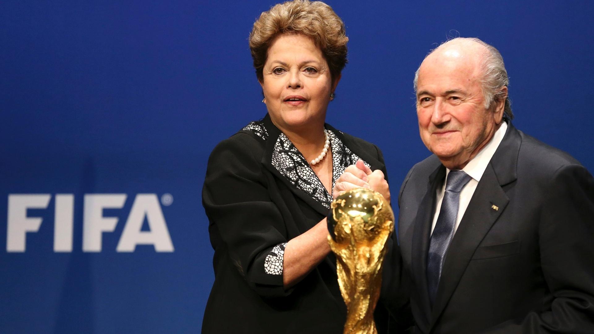 23.jan.2014 - Dilma e Blatter posam para foto atrás de troféu da Copa do Mundo