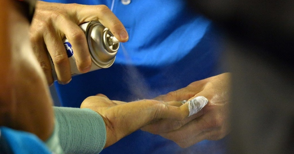 24.jan.2014 - Médico do Aberto da Austrália aplica spray na mão machucada de Rafael Nadal
