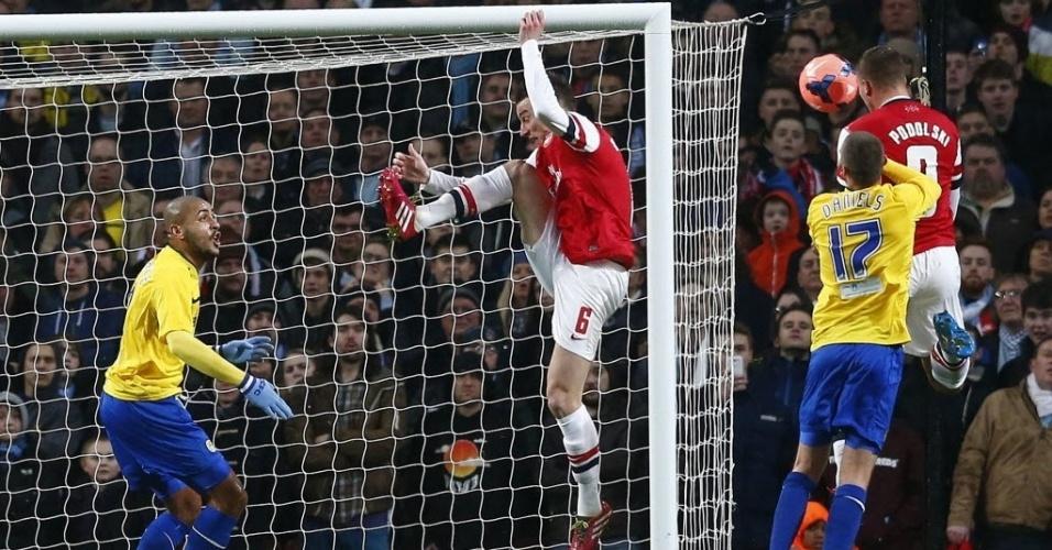 24.jan.2014 - Podolski desvia a bola e marca o segundo do Arsenal na partida contra o Coventry City, pela Copa da Inglaterra