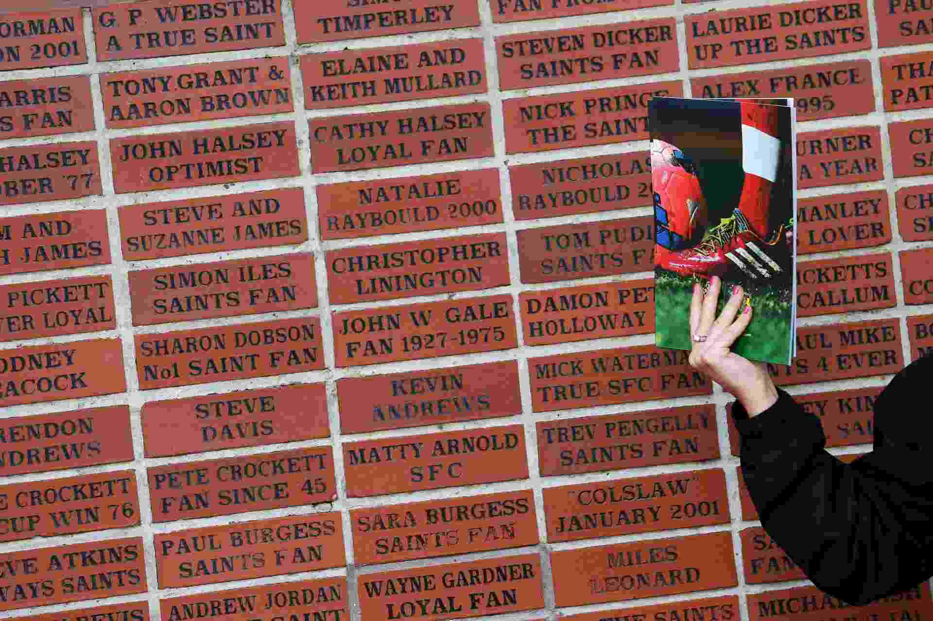 Mulher vende programa para Southampton Yeovil Town, pela Copa da Inglaterra. Atrás, painel com nome de torcedores - REUTERS/Stefan Wermuth