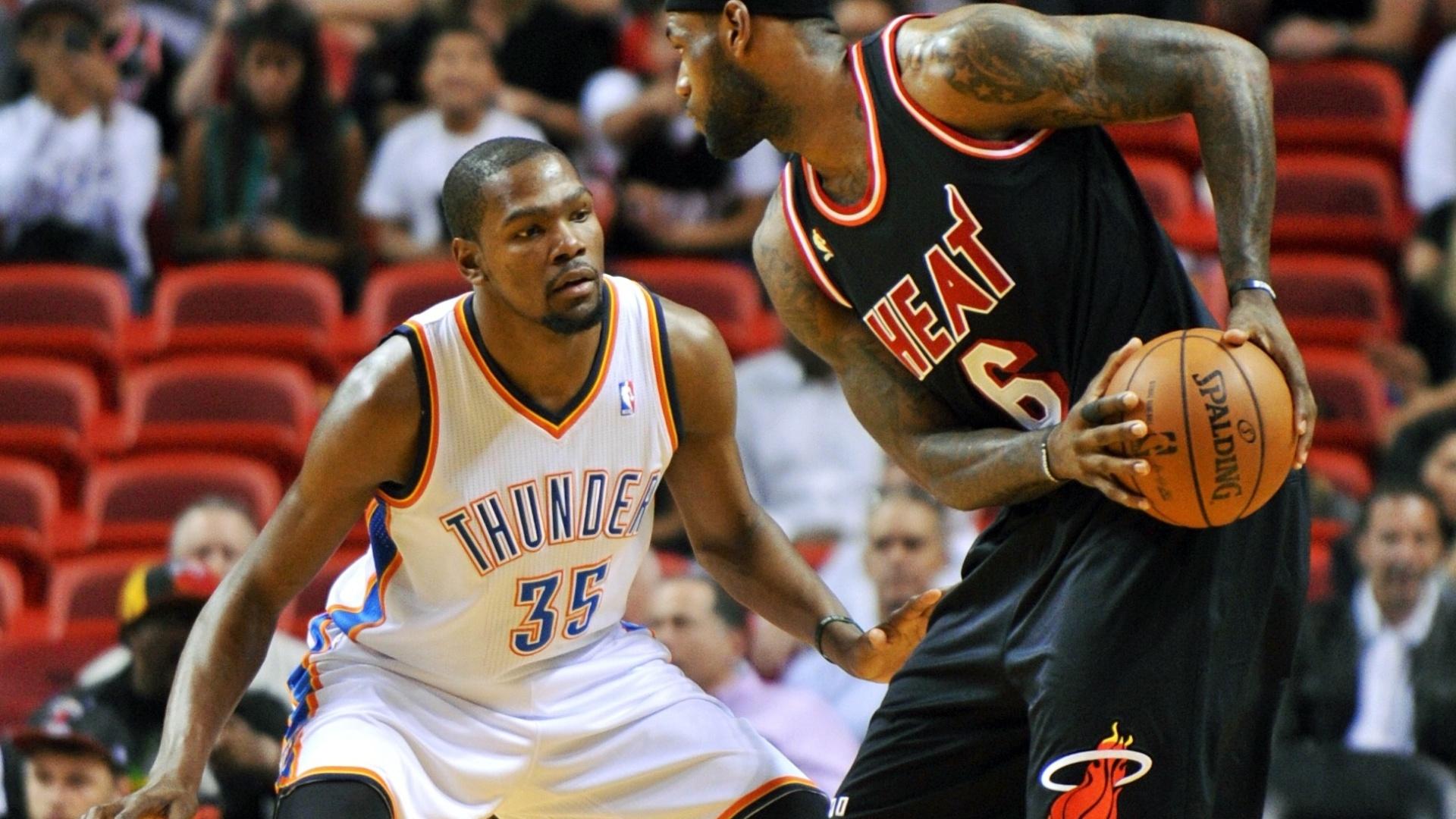 30.jan.2014 - LeBron James tenta encarar a marcação de Kevin Durant durante jogo entre Heat e Thunder