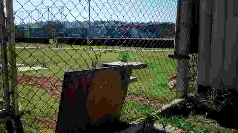 Seguranças do Corinthians tentaram usar tapumes de madeira para tapar o buraco feito pelos torcedores no alambrado do CT Joaquim Grava - Karla Torralba/UOL