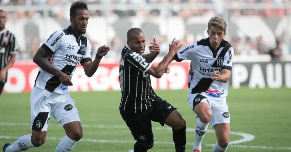 02.fev.2014 - Corintiano Emerson Sheik tenta escapar da marcação da Ponte Preta no jogo válido pelo Campeonato Paulista