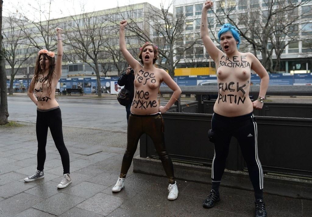 07.fev.2014 - Em Berlim, na Alemanha, três mulheres deixam os seios a mostra e exibem mensagens de protesto contra a homofobia na Rússia, local sede das Olimpíadas de Inverno
