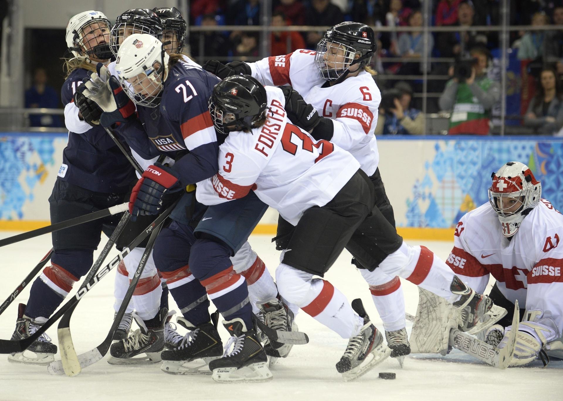 10.02.14 - Americanas e suíças lutam pelo puck; time feminino dos Estados Unidos goleou por 9 a 0
