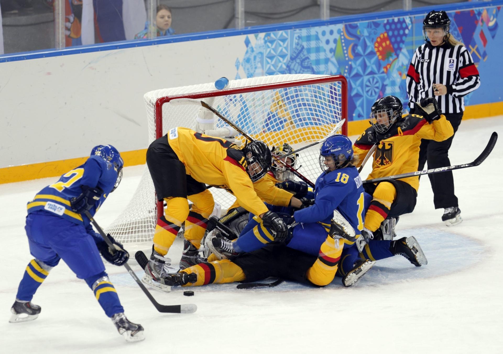 11.02.14 - Jogadoras da Suécia e da Alemanha fazem de tudo para ter a posse do disco em partida de hóquei feminino em Sochi (Rússia)