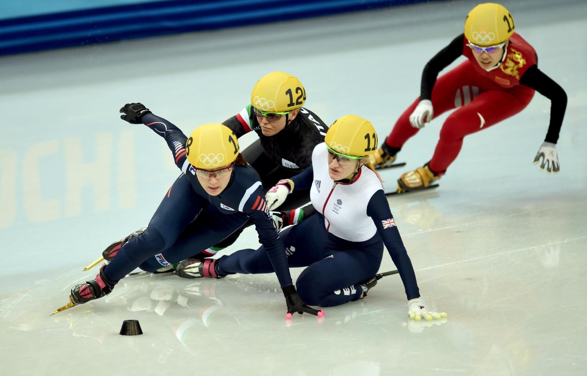 13.02.14 - Elise Christie, de branco, derruba as adversárias Park Seung-Hi (azul) e Arianna Fontana (preto); ela levou a prata na prova de patinação de velocidade em pista curta, mas acabou desclassificada.  A chinesa Li Jianrou saiu da quarta posição para conquistar o ouro após a queda das rivais