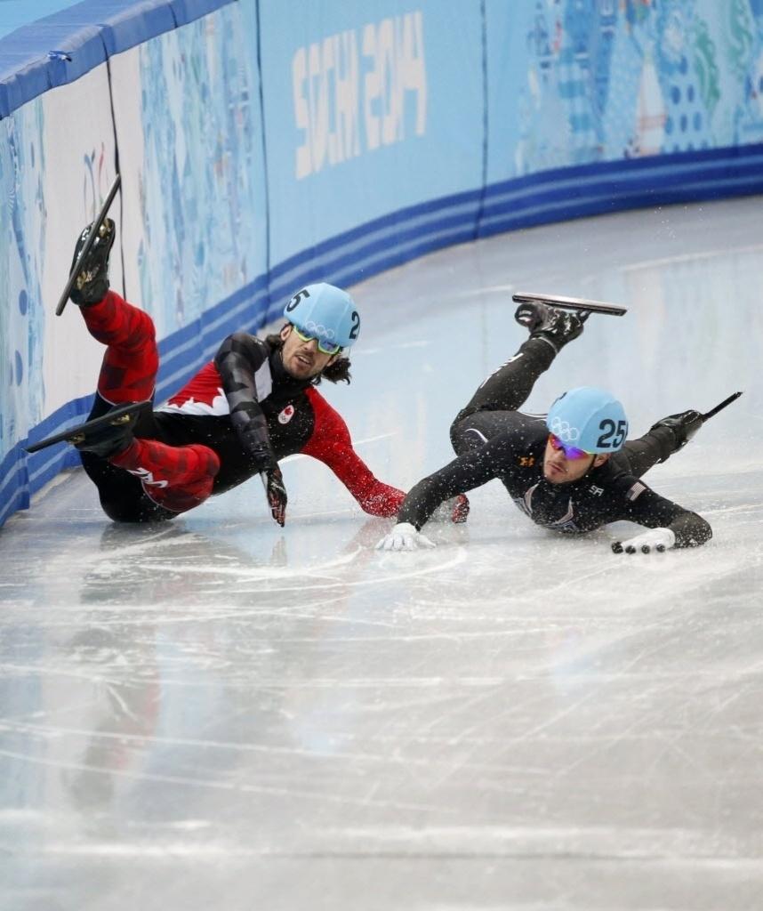 Canadense Charles Hamelin e o americano Eduardo Alvarez deslizam depois de caírem na pista de gelo na patinação em velocidade
