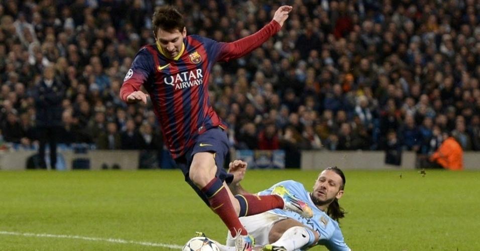 18.fev.2014 - Demichelis, do Manchester City, comete pênalti em Messi, do Barcelona, pelas oitavas de final da Liga dos Campeões