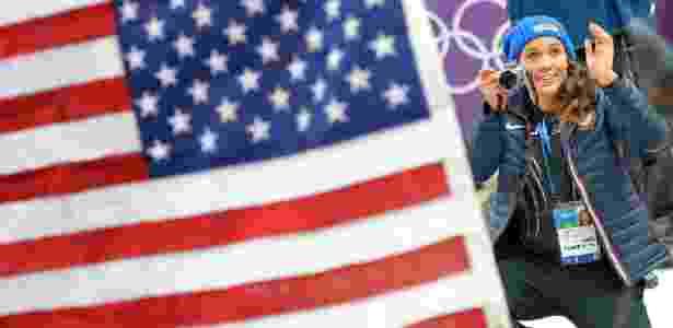 19.fev.2014 - Norte-americana Lolo Jones tira fotos das compatriotas no pódio do bobsled de duplas feminino - AFP PHOTO / LEON NEAL