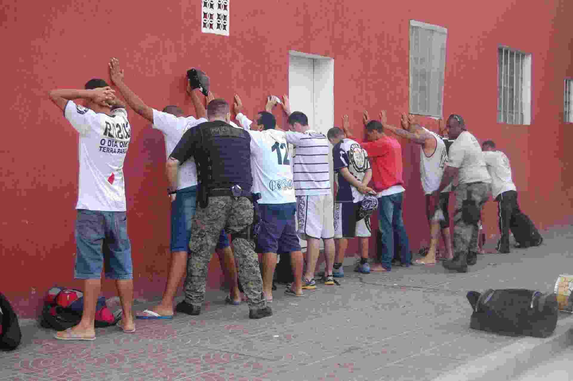 20.fev.2014 - A Polícia Civil de São Paulo deteve na manhã desta quinta-feira (20) ao menos dez torcedores suspeitos da invasão do Centro de Treinamento do Corinthians, ocorrida no início do mês. Nove dos suspeitos foram levados à sede do Departamento de Homicídios e Proteção à Pessoa (DHPP) para averiguação e um deles foi preso e algemado por porte de arma, um revólver calibre 38. - HÉLIO TORCHI/ESTADÃO CONTEÚDO