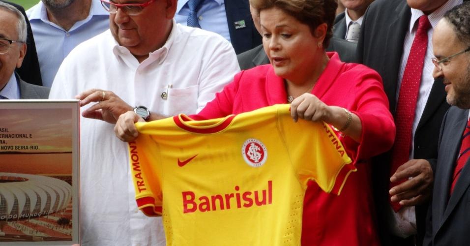 20.fev.2014 - Dilma Rousseff mostra camisa amarela do Inter, feita em homenagem ao ano de Copa do Mundo no Brasil