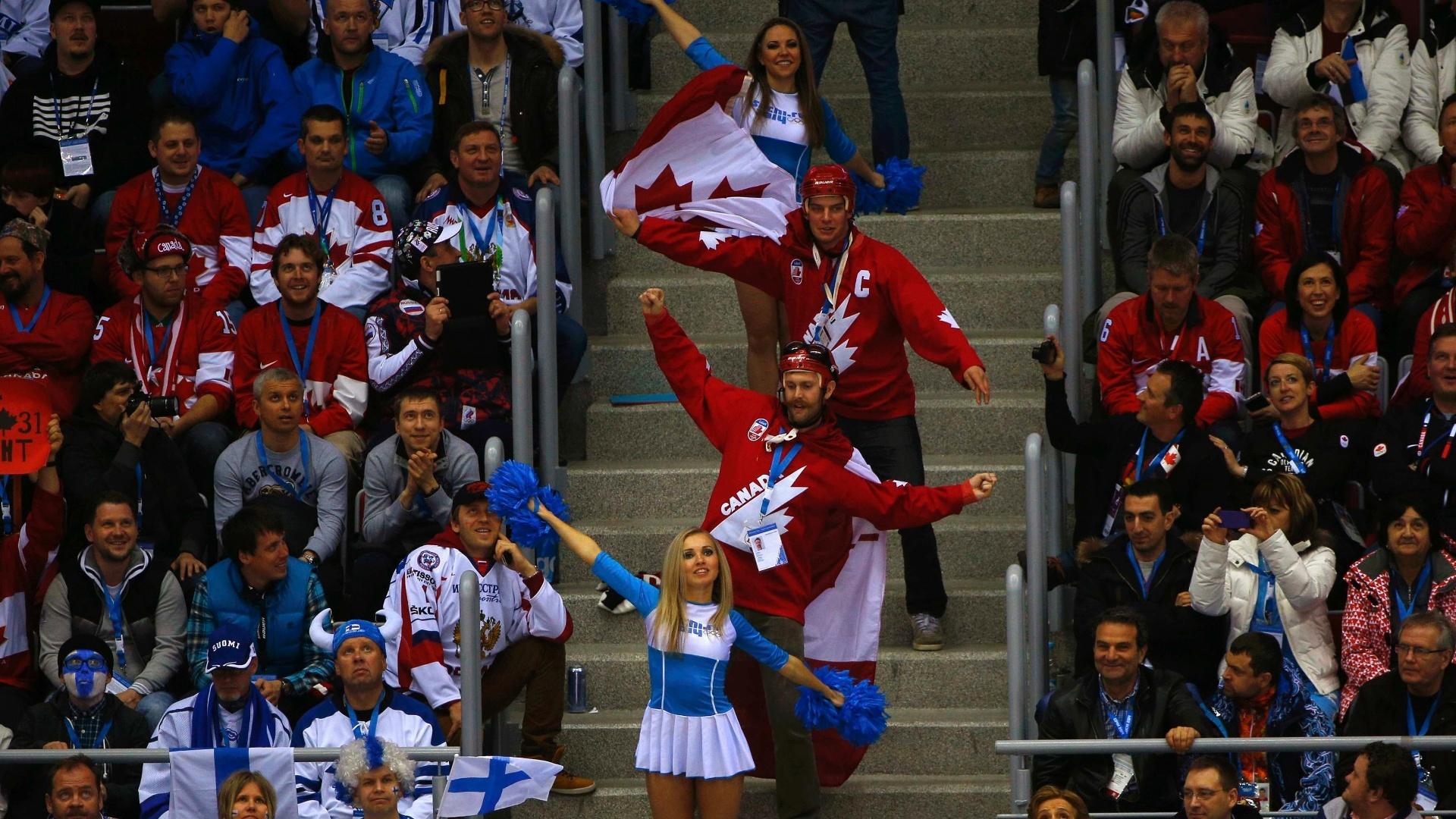 16.02.14 - Torcida canadense faz graça com cheerleaders durante jogo entre Canadá e Finlândia pelo hóquei no gelo masculino