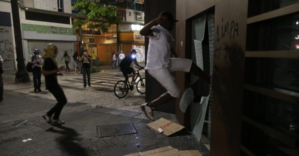 22. fev. 2014 - Manifestante chuta porta de estabelecimento durante protesto anti-Copa