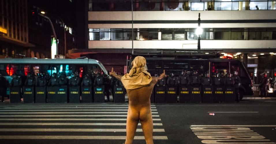 22.fev. 2014 - Pelado, manifestante mostra dedo do meio para os policiais durante manifestação em São Paulo