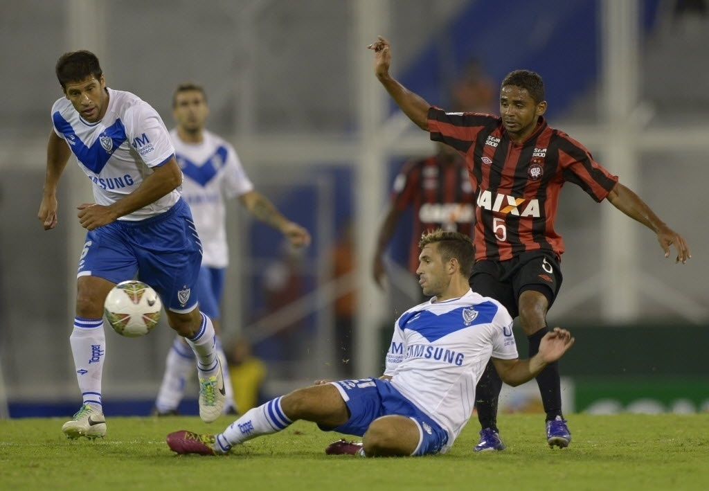 25.fev.2014 - Deivid, do Atlético-PR marca Agustin Allione, do Vélez Sarsfield, pela Copa Libertadores