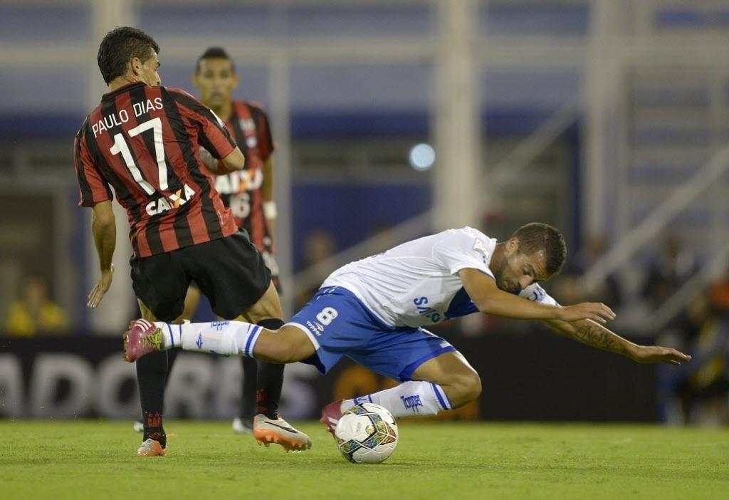 25.fev.2014 - Hector Canteros, do Vélez Sarsfield, cai após dividida com Paulinho Dias, do Atlético-PR, pela Copa Libertadores