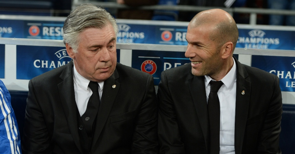26.fev.2014 - Treinador do Real Madrid Carlo Ancelotti conversa com o agora assistente-técnico Zinedine Zidane antes da partida contra o Schalke 04, pela Liga dos Campeões