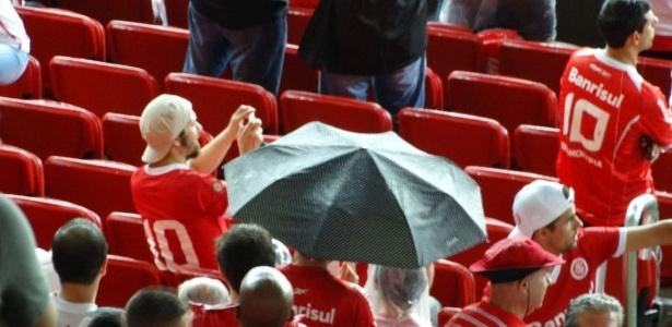 Torcedor do Inter abre guarda-chuva para se proteger da água que caia em fresta da cobertura do Beira-Rio