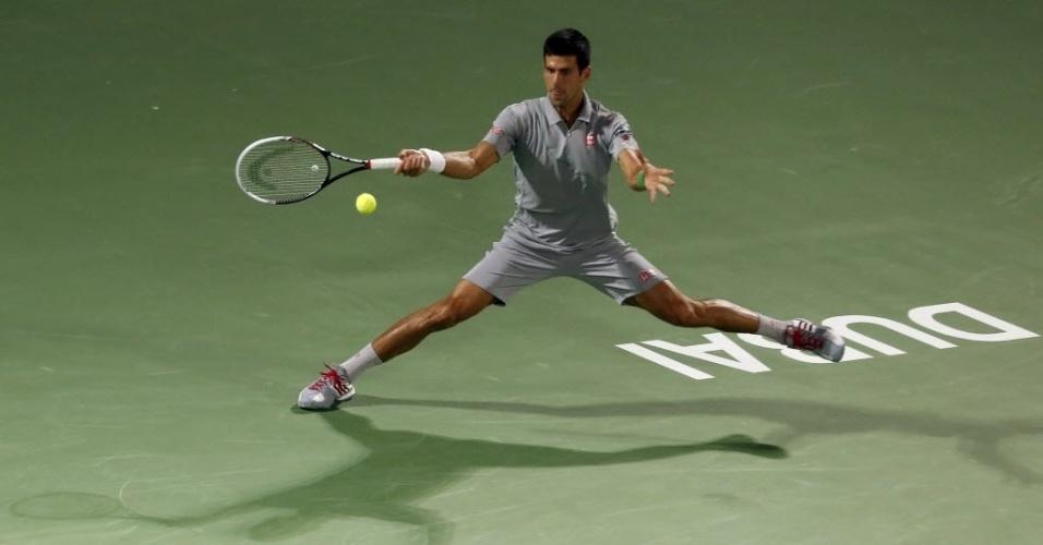 28.fev.2014 - Novak Djokovic estica as pernas para chegar na bola durante a semifinal do Torneio de Dubai contra Roger Federer