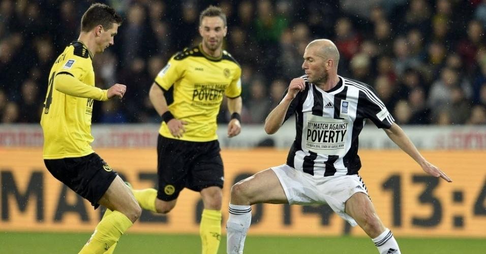 04.mar.2014 - Estrela do evento junto com Ronaldo, Zinedine Zidane aplica drible sobre jogador do Young Boys