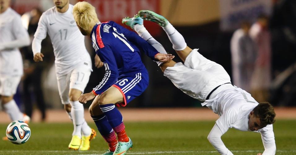 05.03.2014 - Tyler Boyd, da Nova Zelândia, fica de ponta cabeça ao tentar marcar o loiro Hotaru Yamaguchi, do Japão, durante amistoso preparatório para Copa do Mundo