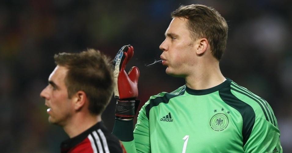 05.mar.2014 - Ao lado do capitão Philipp Lahm, goleiro da Alemanha, Manuel Neuer, cospe na luva. Os alemães venceram o Chile por 1 a 0 no último amistoso antes da Copa