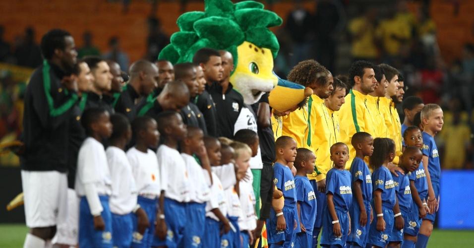 05.mar.2014 - Jogadores de Brasil e África aguardam o hino nacional ao lado dos mascotes Zakumi e Fuleco, das Copas de 2010 e de 2014 respectivamente