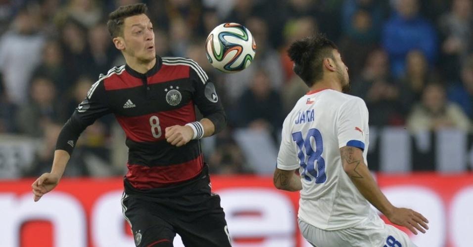 05.mar.2014 - Mesut Özil, meia da Alemanha, disputa pela bola com Gonzalo Jara, do Chile, no último amistoso antes da Copa do Mundo