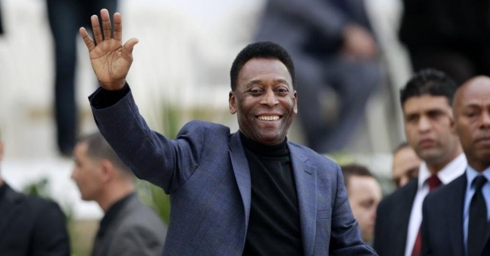 05.mar.2014 - Pelé acena para os fãs que foram assistir ao amistoso entre Argélia e Eslovênia. O ex-jogador brasileiro deu o pontapé inicial da partida em uma campanha para promover um campeonato de futebol para jovens da marca Coca-Cola.