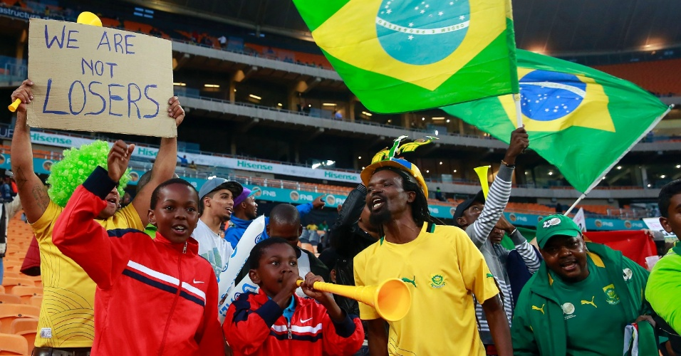 """05.mar.2014 - Pequenos torcedores também marcam presença no Soccer City para o amistoso entre Brasil e África do Sul; ao fundo, torcedor exibe um cartaz dizendo: """"Nós não somos perdedores"""""""