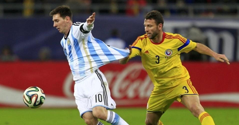05.mar.2014 - Romeno Razvan Rat Dinca puxa a camisa do argentino Messi durante amistoso disputado em Bucareste