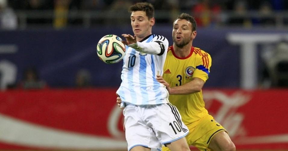05.mar.2014 - Sob marcação, Messi tenta dominar a bola durante o amistos entre Argentina e Romênia