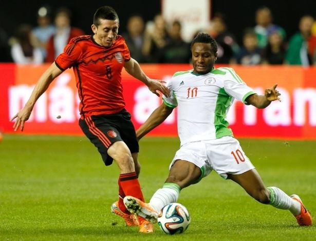 05.mar.2014 - John Obi Mikel, da Nigéria, tenta desarmar Herrera, do México, em amistoso disputado nos EUA; o México estreia o uniforme reserva para a Copa
