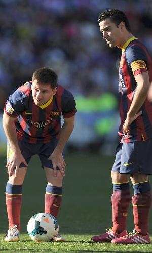 08.03.2014 - Messi agacha para ajeitar a bola visando uma cobrança de falta e é observado por Xavi