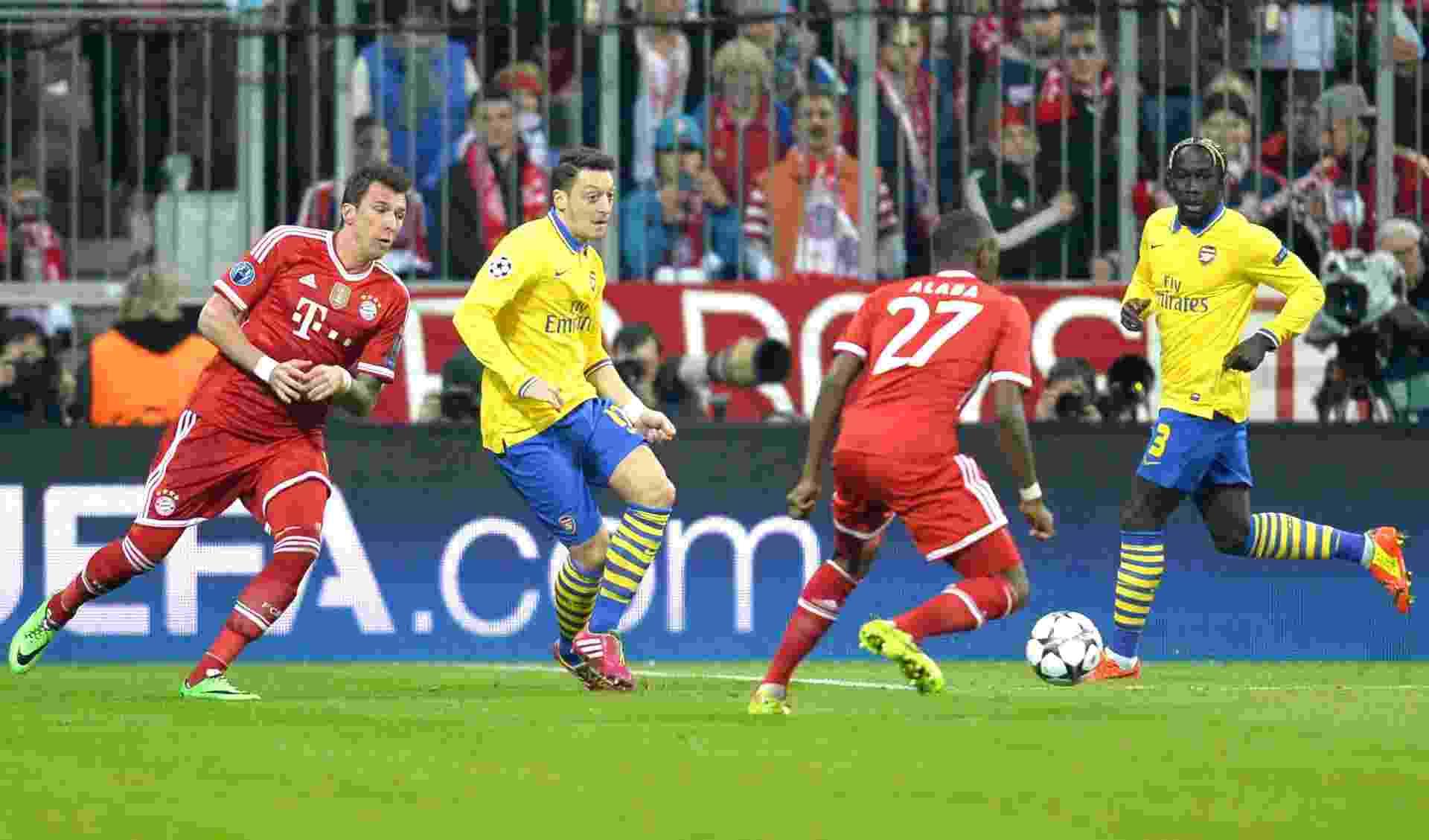 11.mar.2014 - Cercado por jogadores do Bayern de Munique, Özil, do Arsenal, tenta passe - AFP PHOTO / ODD ANDERSEN