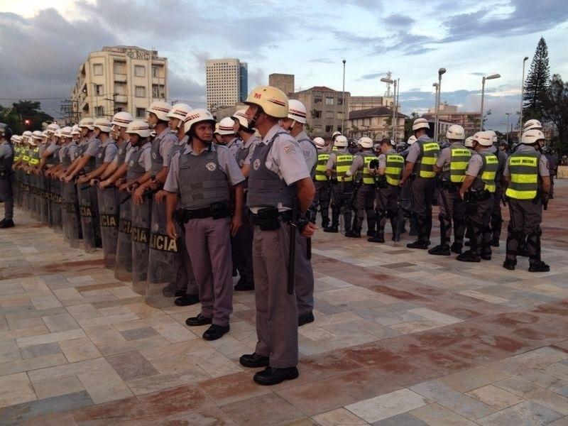 13.mar.2014 - Barreira de policiais controla o espaço em que manifestantes fazem protesto contra a Copa-2014 em São Paulo