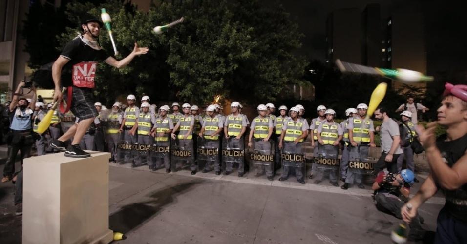 13.mar.2014 - Em meio ao protesto anti-Copa, manifestante fazem malabarismo ao lado de barreira da PM