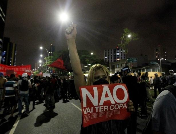 """13.mar.2014 - Garota, com faixa na boca, levanta cartaz com os dizerem """"não vai ter Copa"""" em São Paulo"""