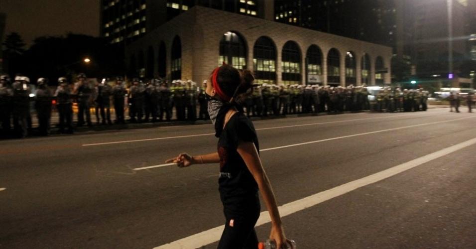 13.mar.2014 - Garota faz gesto vulgar contra os policiais durante protesto anti-Copa em SP