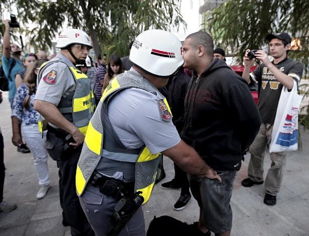 13.mar.2014 - Policiais revistam manifestantes que participam do protesto anti-Copa em São Paulo