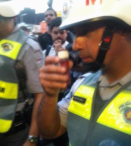 13.mar.2014 - Policial cheira suposto potinho de vinagre durante protesto anti-Copa em São Paulo