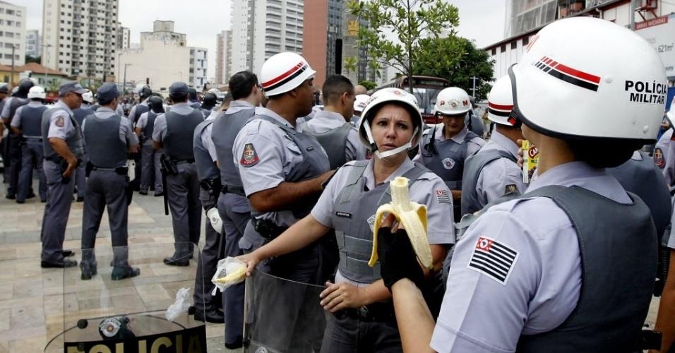 13.mar.2014 - Policial come banana enquanto espera o início do protesto anti-Copa em São Paulo
