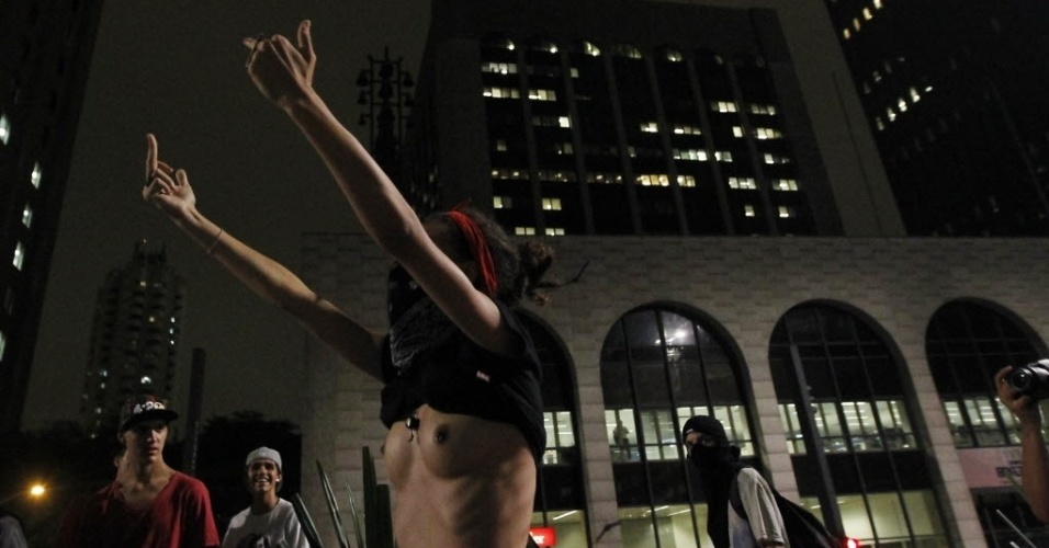 13.mar.2014 - Seminua, garota faz gesto vulgar contra os policiais durante protesto anti-Copa em SP
