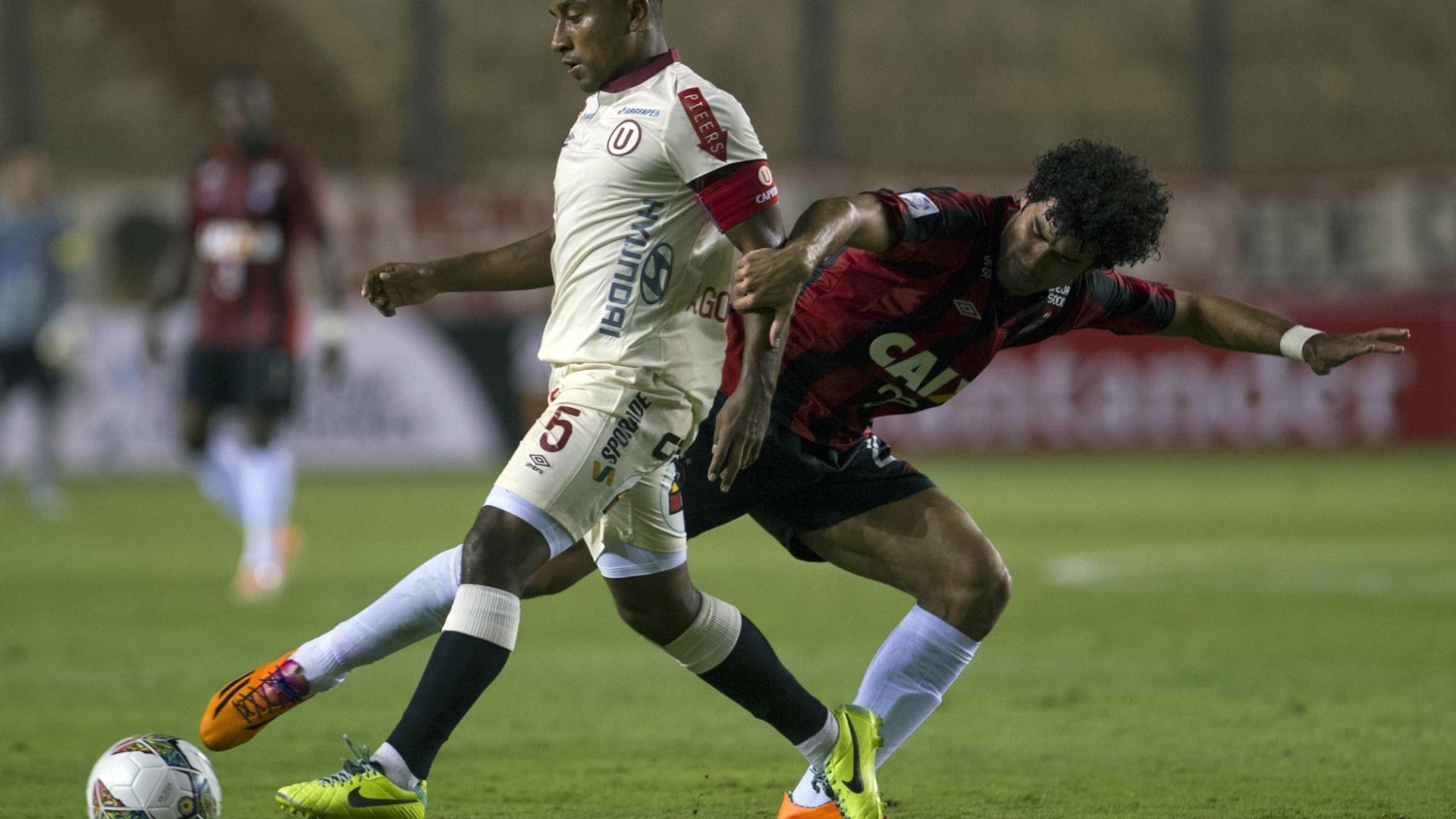 14.03.14 - Bruno Mendes tenta o desarme sobre Antonio Gonzales durante partida entre Atlético-PR e Universitário pela Libertadores