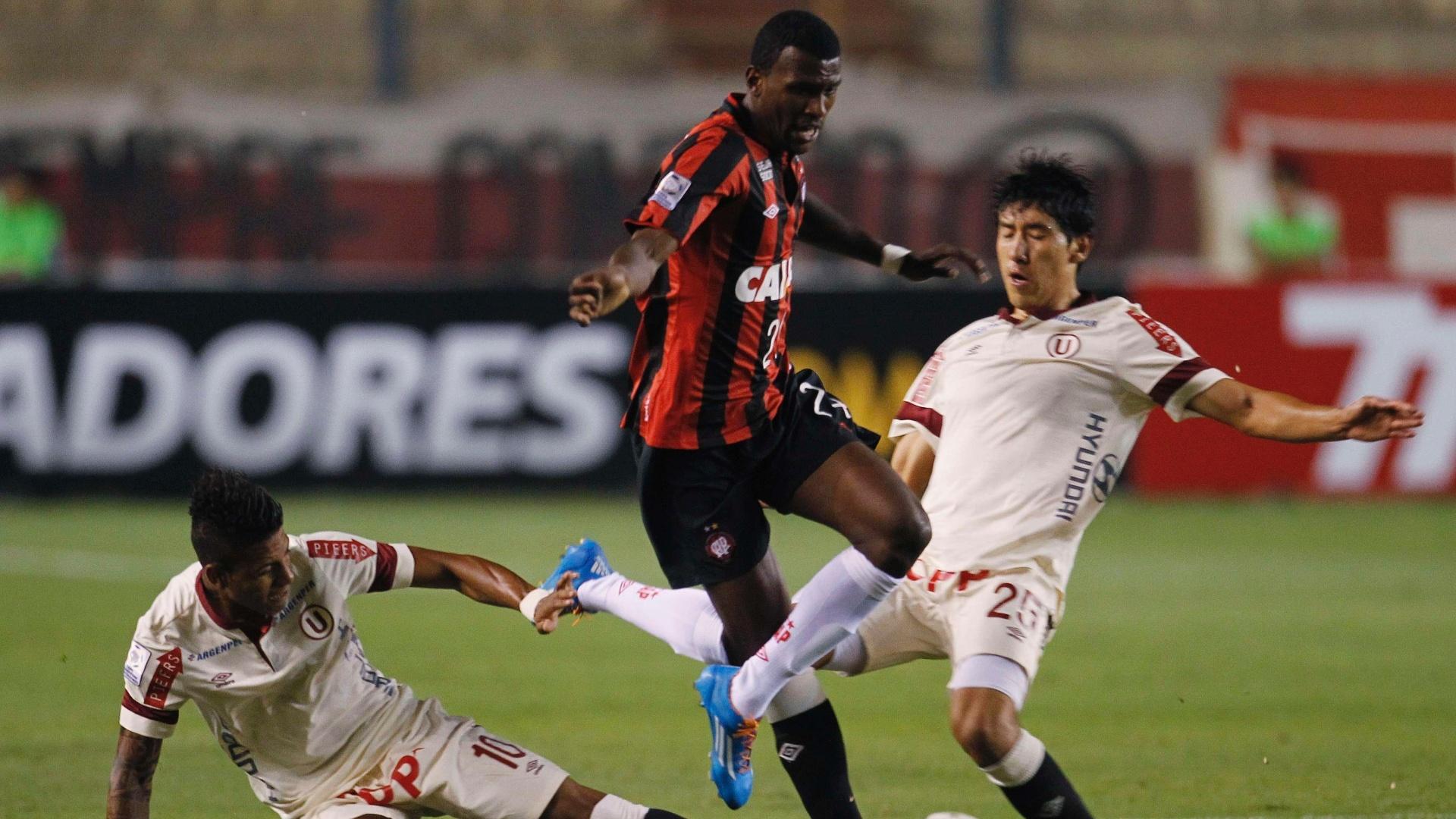 14.03.14 - Douglas Coutinho tenta escapar da marcação de dois jogadores durante partida entre Atlético-PR e Universitário pela Libertadores