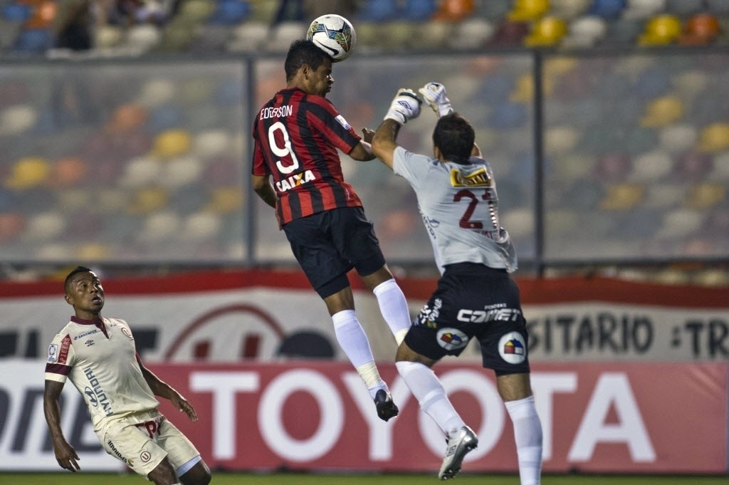 14.03.14 - Ederson cabeceia a bola na partida entre Atlético-PR e Universitário pela Libertadores
