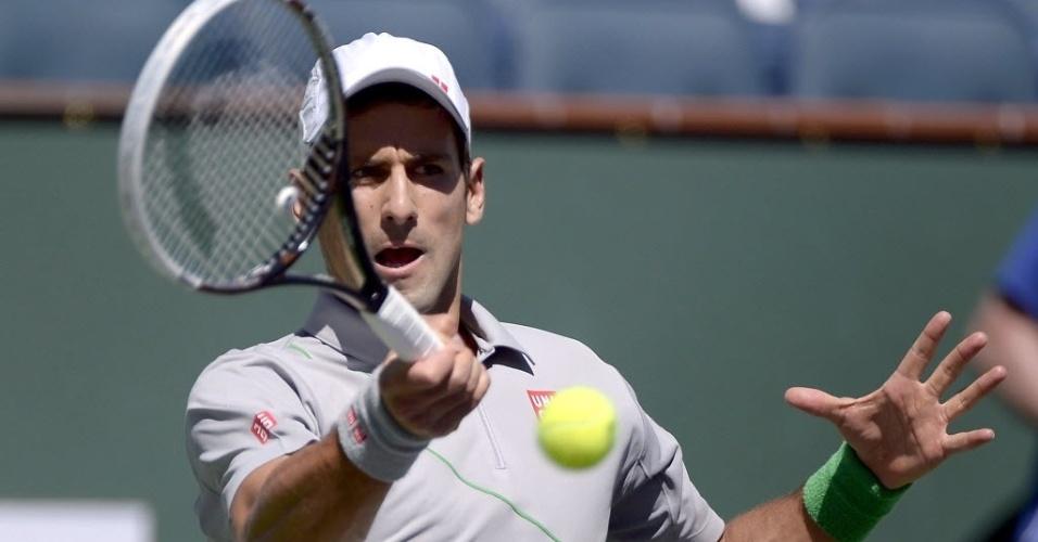 14.mar.2014 - De forehand, Novak Djokovic golpeia a bola no duelo com Julien Benneteau